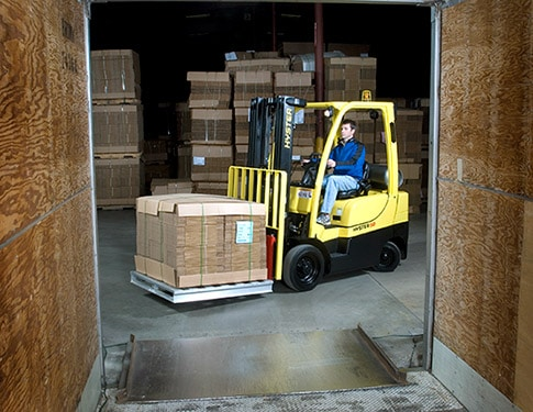 Forklift loading goods into the back of a truck